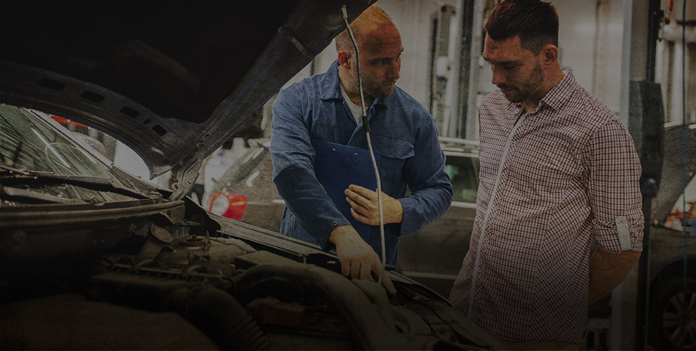 mechanic showing customer something under the bonnet of a car